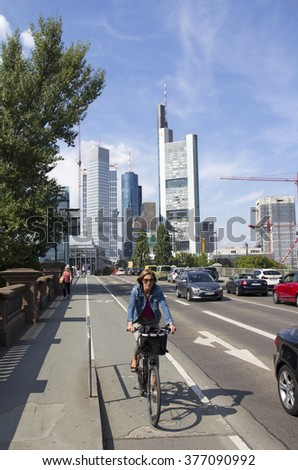 Frankfurt, Germany - August 29, 2013: Woman on a bicycle and car traffic  drive on a bridge across the Main river with tall office buildings in the background in Frankfurt, Germany on August 29, 2013. - stock photo