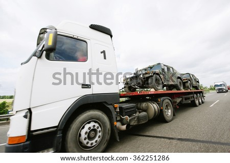 FRANKFURT, GERMANY - JUL  4, 2011: Truck carrying lightweight armored vehicles on a public highway