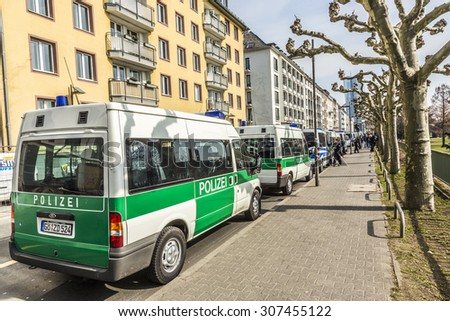 FRANKFURT, GERMANY - MAR 18, 2015: police parks cars near demonstration against EZB and Capitalism in Frankfurt, Germany. 30 tsd. people join the demo. - stock photo