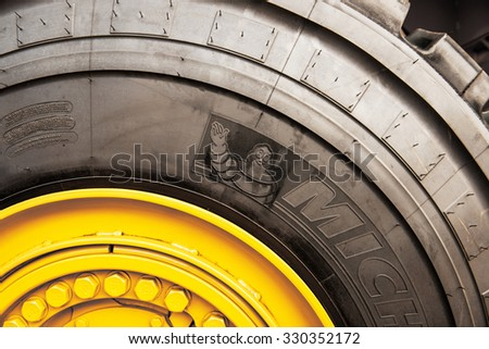 FRANKFURT, GERMANY - SEPTEMBER 05, 2014: Detail of immense Michelin tire on yellow tractor. Michelin is a tire manufacturer based in France - stock photo