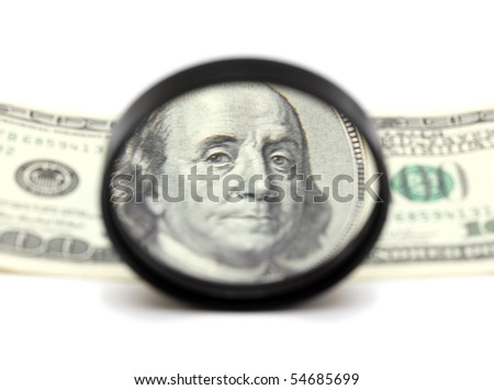 franklin on hundred dollars through magnifying glass - stock photo