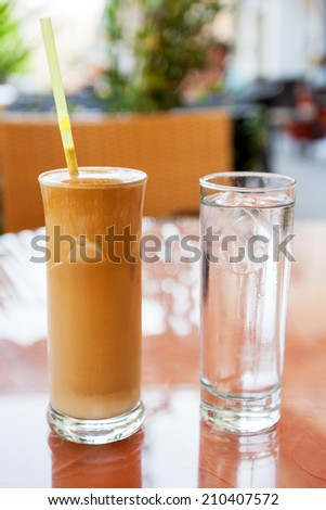 Frappe with a glass of water on cafe table. Crete, Greece  - stock photo