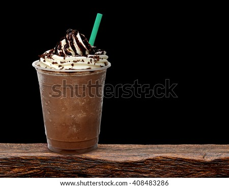 Frappuccino in takeaway cup on wooden table isolated on black - stock photo