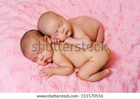 Fraternal twin newborn baby girls sleeping on pink, three dimensional rose fabric. One baby is lying on her stomach and the other is propped on top of her sister.