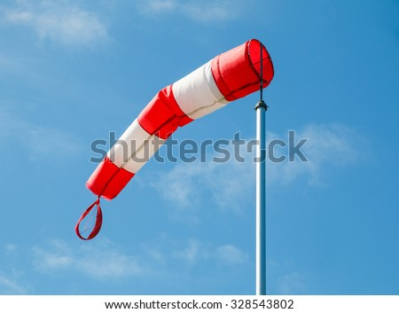 Frayed windsock in moderate wind against blue sky with few clouds - stock photo