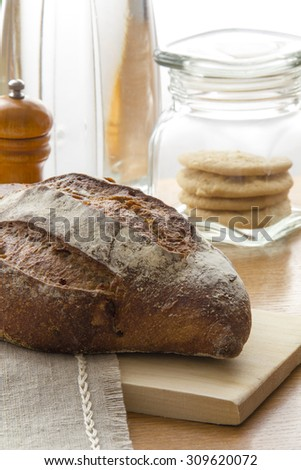 Freash Tradition bread loaf on the kitchen table with cakes jar and kitchen utensils