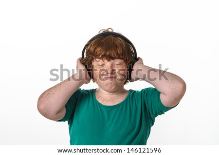 Freckled red-hair boy listening music. Isolated on white background.