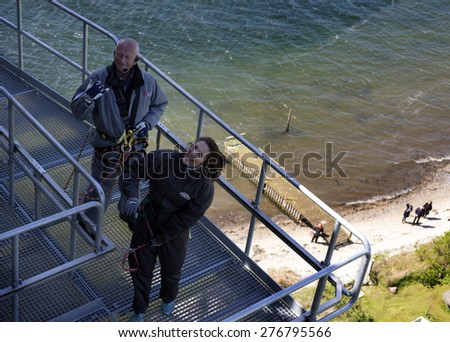 FREDERICIA, DENMARK - MAY 10, 2015: Bridgewalking Littlebelt. Official opening day. Crown Princess Mary and Bridgewalkingchef, Knud Jeppesen on the bridge and people on the beach. - stock photo