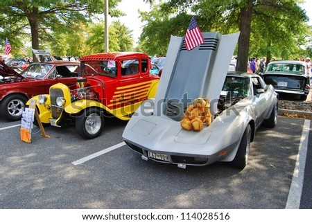 FREDERICK, MD- SEPTEMBER 16: 1962 Yellow Red Ford Coupe, and  1979 Silver Chevrolet Corvette on Sept. 16, 2012 in Frederick , MD USA. Alzheimer's Association Benefit Car Show at MVA in Maryland. - stock photo