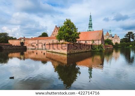 Frederiksborg castle reflected in the lake in Hillerod, Denmark. Renaissance castle and romantic pond near Copenhagen. - stock photo
