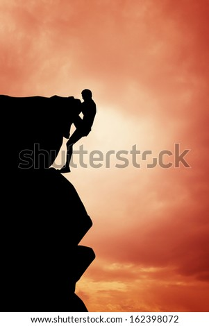 Free climbing man at sunset - stock photo