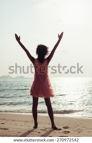 Free girl enjoying freedom feeling happy at beach at sunset. Beautiful serene relaxing woman in pure happiness and elated enjoyment with arms raised outstretched up. Latin Caucasian female model. - stock photo