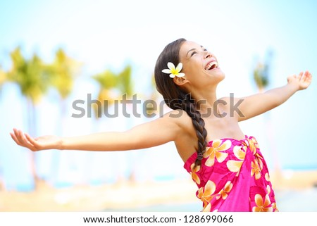 Free happy elated beach woman in freedom joy concept. Beautiful girl smiling with arms out looking up joyful on Hawaiian beach. Mixed race Asian / Caucasian girl. - stock photo
