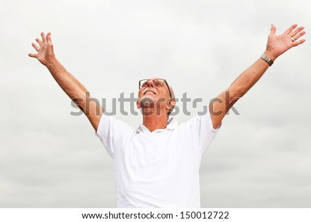 Free happy retired senior man with beard and glasses enjoying the outdoors with cloudy sky. - stock photo