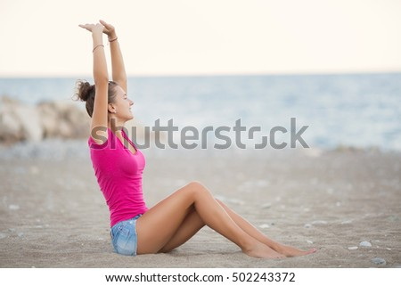 Free Happy Woman Enjoying sunset at beach. Romantic Girl Outdoor. Freedom concept. Enjoyment. Back view of young woman with hands up watching at ocean. Girl sit at sand beach seaside. summer lifestyle