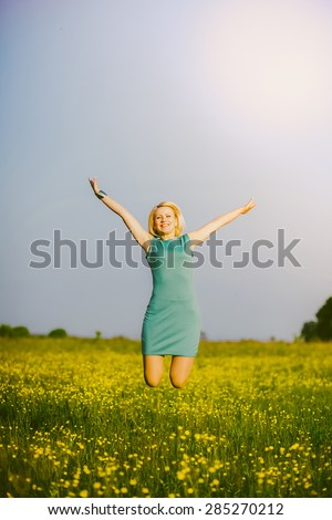 Free happy woman jumping in summer field. Feeling grate. Beautiful blonde girl in nature landscape. Summer or spring day. Successful person celebrating success. Field flowers. Hands outstretched up. - stock photo