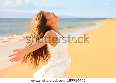 Free happy woman on beach enjoying nature. Natural beauty girl outdoor in freedom enjoyment concept. Mixed race Caucasian Asian girl posing on travel vacation holidays in dress. - stock photo
