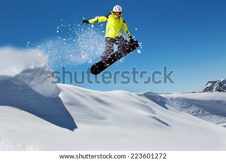 Free rider with snowboard jumping from hill - stock photo
