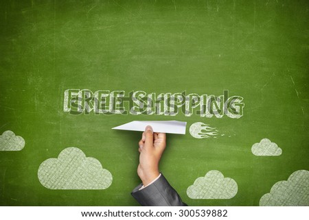 Free shipping concept on green blackboard with businessman hand holding paper plane - stock photo