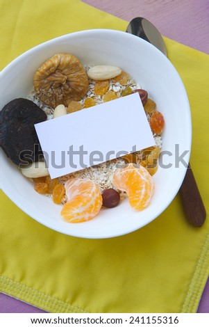 Free space for a text on the plate with healthy breakfast:Food background: dried figs,tangerine,raisins,oat flakes,almonds,nuts,hazelnuts. The plate is placed on an orange napkin on a violet surface. - stock photo