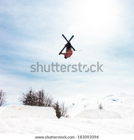 Free style skier performing a high up in the sky back flip jump. Snow covered mountains in the background. - stock photo