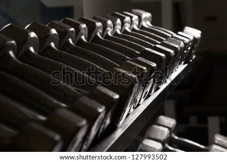 Free weights sitting on a weight rack. Dark intensity. - stock photo