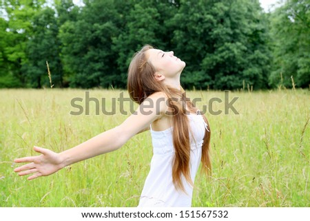 Free young woman on the meadow breathes in deeply - stock photo
