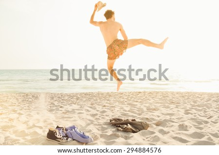 Freedom! A young man getting rid of clothes on a hot summer day, jumping up in swimwear running to the sea to jump into the water and swim - stock photo