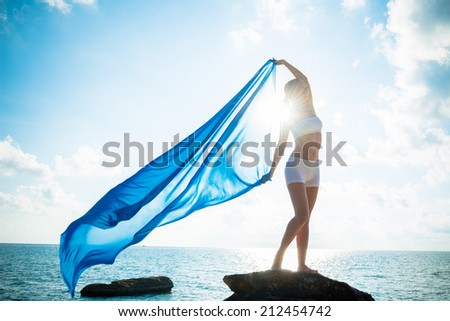 Freedom and beauty concept. Beautiful girl with blue scarf standing on the Rock - stock photo