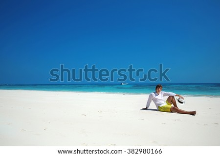 Freedom beach. Relax. Successful handsome man in hat resting on exotic seashore with blue water and white sand. Summer Vacation Travel. Bliss concept.  - stock photo