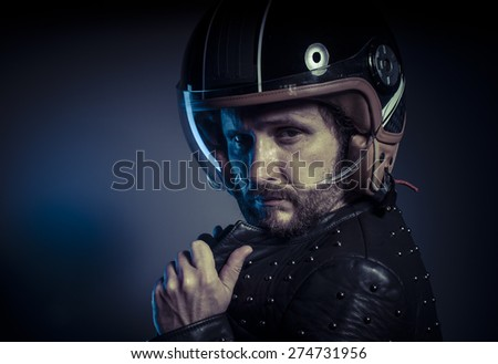 Freedom, biker with motorcycle helmet and black leather jacket, metal studs - stock photo