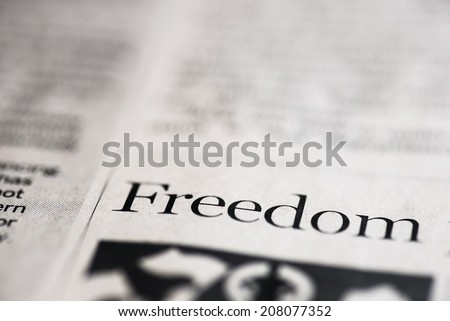 Freedom. Freedom written on real newspaper with shallow dof.