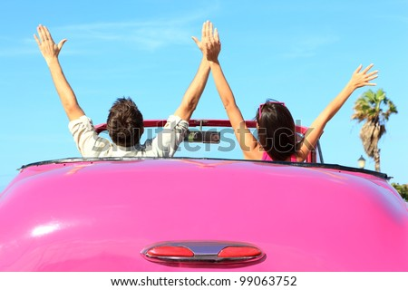 Freedom - happy free couple in car driving in pink vintage retro car cheering joyful with arms raised. Friends going on road trip travel on summer day under sun blue sky. - stock photo