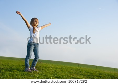 Freedom, little girl playing on meadow - stock photo