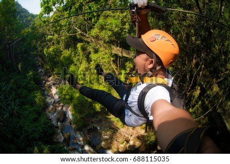 Freedom Male Tourist Wearing Casual Clothing On Zip Line Or Canopy Experience In Laos Rainforest