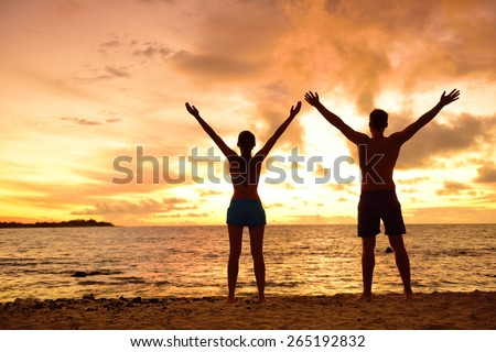 Freedom people living a free, happy, carefree life at beach. Silhouettes of a couple at sunset arms raised up showing happiness and a healthy lifestyle against a colorful sky of clouds background. - stock photo