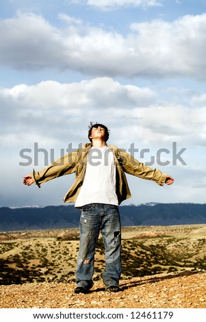 freedom - teenager male with arms wide open, shirt and hair blowing in the wind, standing atop a 1,000 foot cliff