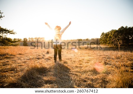 Freedom - This is a shot of a young woman wearing a hat enjoying the wide open spaces. Shot with a warm color tone. - stock photo