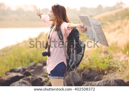 Freedom traveler woman standing with raised arms and enjoying a beautiful nature - stock photo