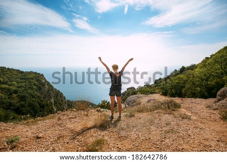 Freedom, Woman standing On Top Of Mountain With Arms Outstretched - stock photo