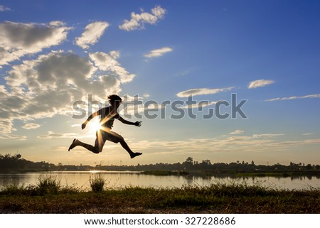 Freedom-young man is jumping at lake with sunset sky - back lit