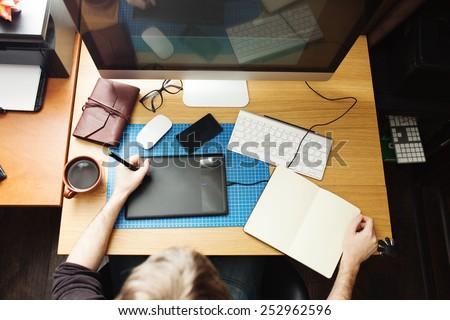 Freelance developer and designer working at home, man using desktop computer.  - stock photo