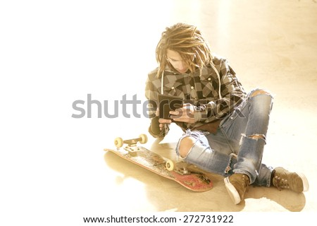 freelance dreadlocks  guy sitting with digital tablet typing message warm filter applied - stock photo