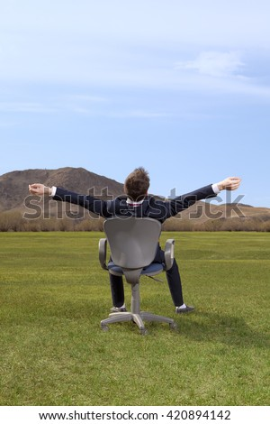 Freelancer. Businessman sitting on chair on green meadow on blue sky background - stock photo