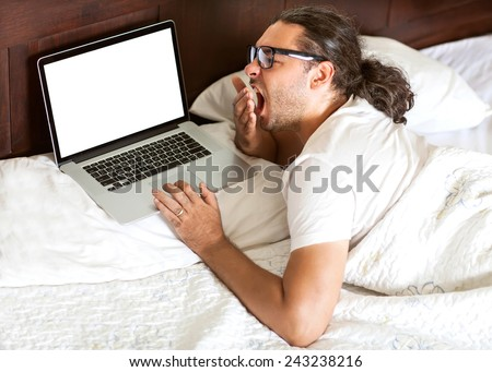 freelancer man with laptop yawns early in the morning in his bed, the work is free earnings, happy business - stock photo