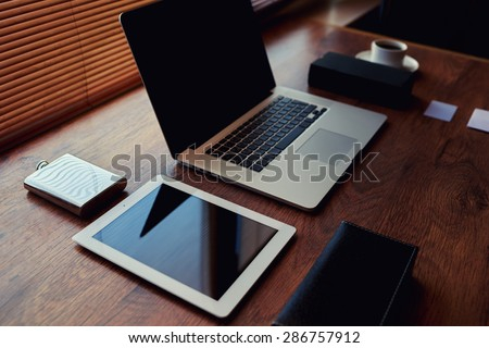 Freelancer needs workstation with luxury accessories, open laptop computer and digital tablet with blank copy space screen at wooden table in home, on-line learning or distance work concept, filter - stock photo