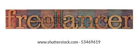 freelancer - word in vintage wood letterpress type blocks stained by color inks, isolated on white - stock photo