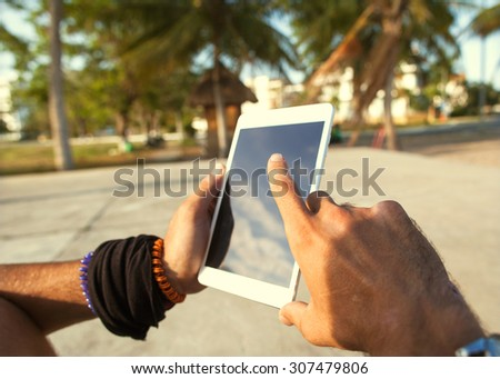 freelancer working guy sitting on the beach with views of palm trees - stock photo