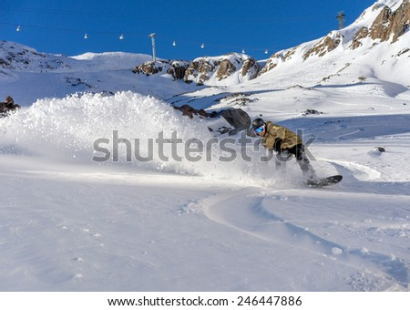 Freerider snowboarder moving down in snow powder on the winter resort