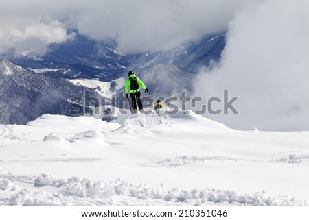 Freeriders on off-piste slope and mountains in mist. Caucasus Mountains, Georgia, ski resort Gudauri.  - stock photo